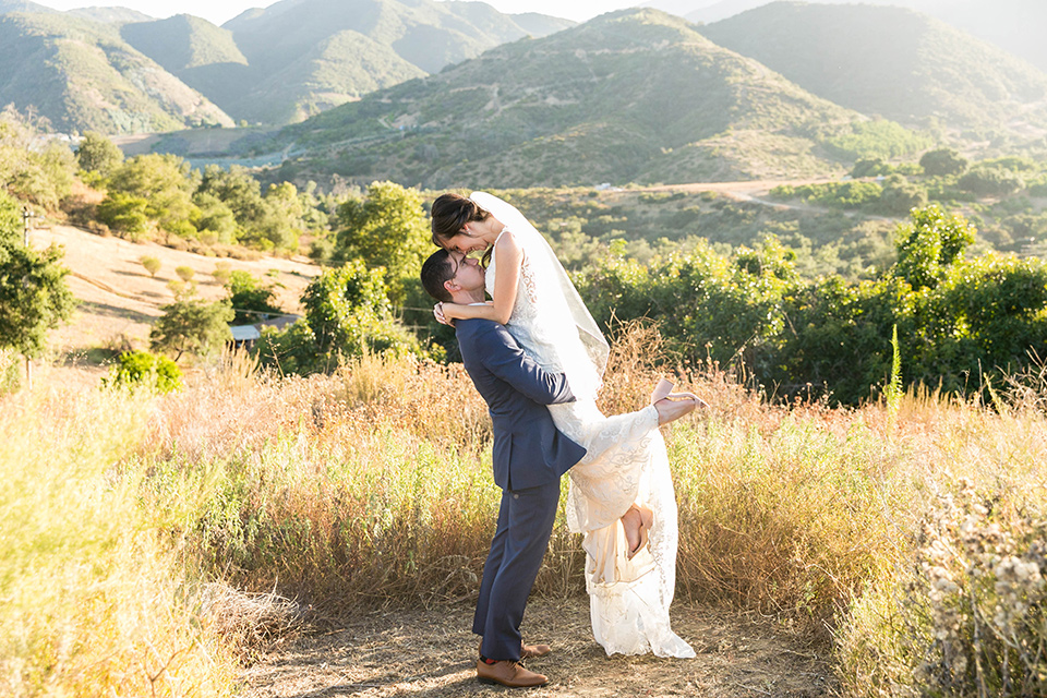 bride in a lace form-fitting gown with straps, the groom in a dark blue suit with a white long tie kissing