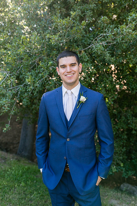 the groom in a dark blue suit with a white long tie