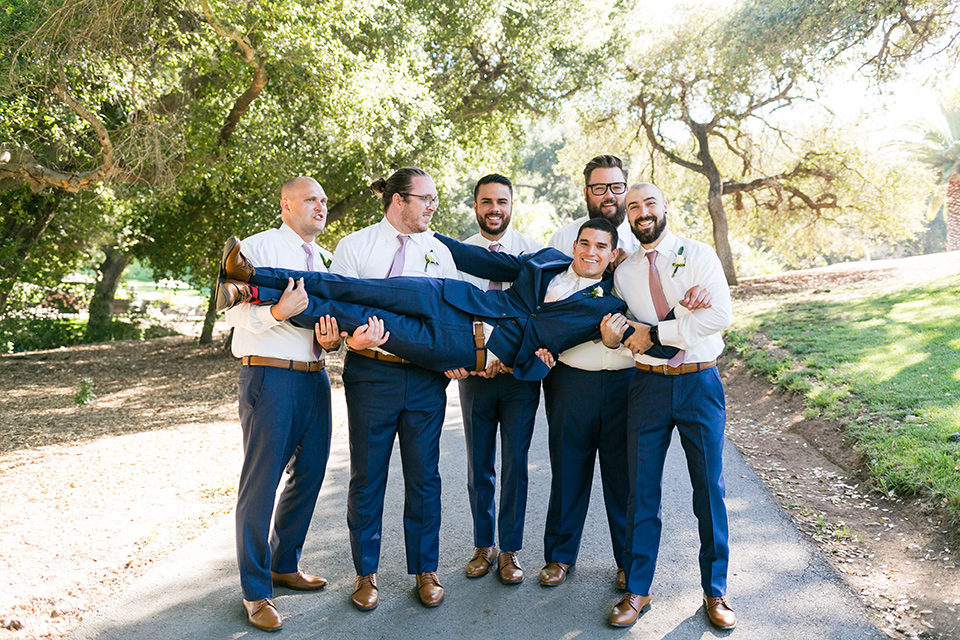 the groom in a dark blue suit with a white long tie and the groomsmen in blue pants and lavender long ties