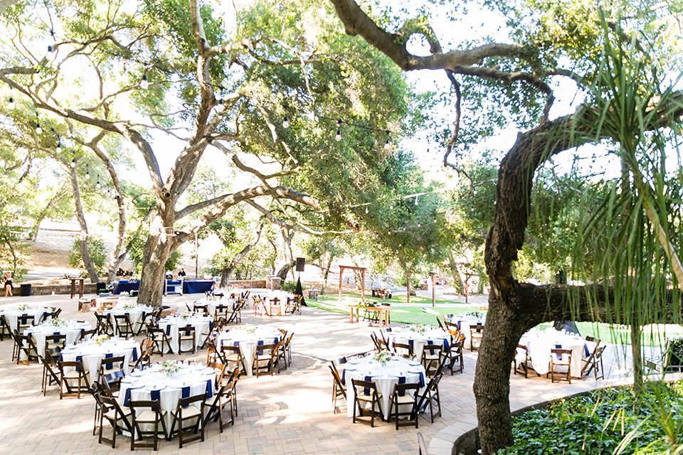 wedding reception with white linens on tables and farmhouse style chairs