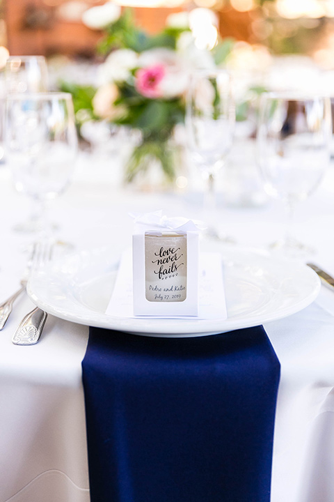 white table linens with blue napkins and gold flatware