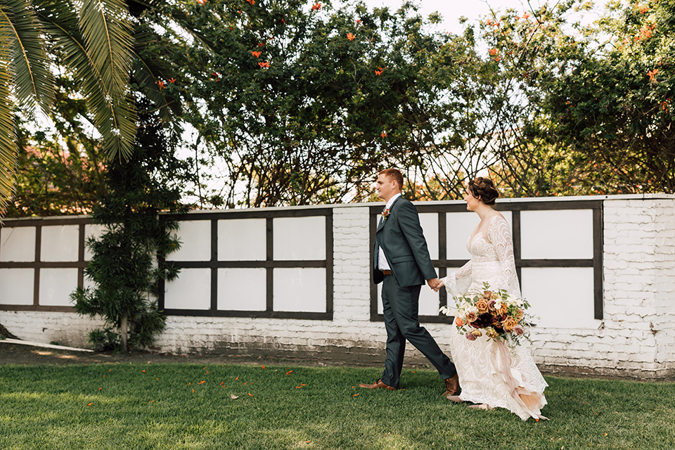 bride in a lace bohemian gown with a high neckline and flutter sleeves, the groom was in grey retail suit with a blue long tie, walking on grass