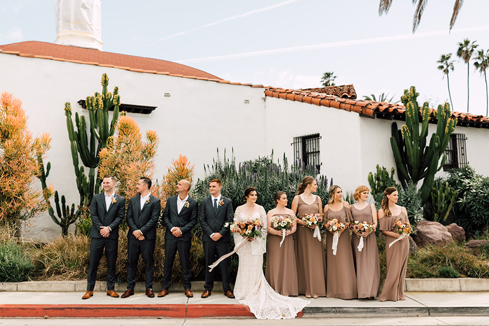bride in a lace bohemian gown with a high neckline and flutter sleeves, the groom was in grey retail suit with a blue long tie, the bridesmaids in taupe neutral gowns and the groomsmen in grey suits for purchase with blue long ties