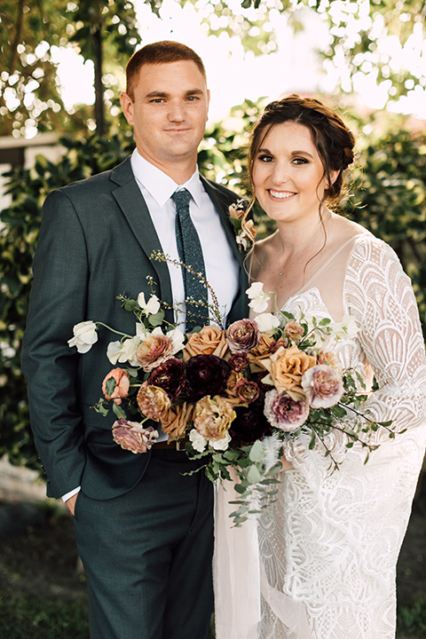 bride in a bohemian style gown with lace, a high neckline, and flutter sleeves, and the groom in a grey suit with a blue long tie