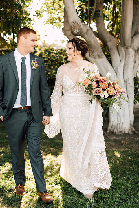 bride in a bohemian style gown with lace, a high neckline, and flutter sleeves groom in a grey suit with a blue long tie