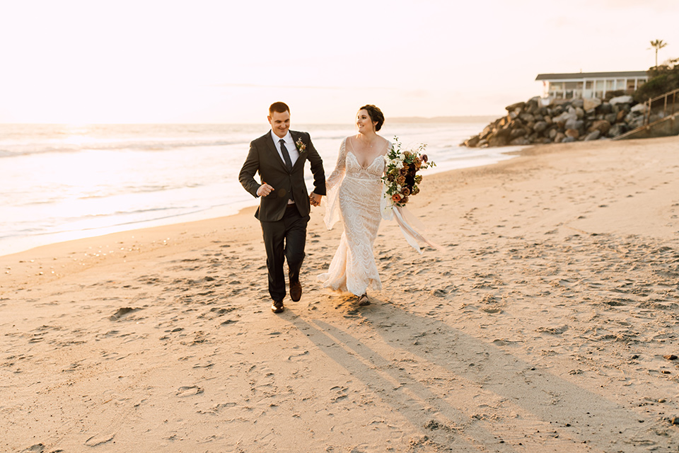 bride in a lace bohemian gown with a high neckline and flutter sleeves, the groom was in grey retail suit with a blue long tie, walking on sand