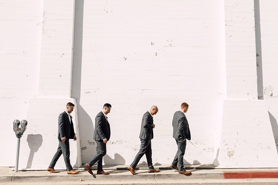 groom and groomsmen in grey suits walking by white brick wall