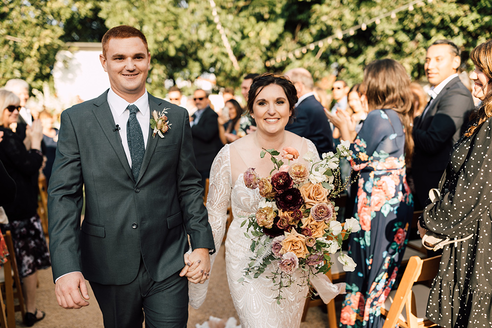 bride in a lace bohemian gown with a high neckline and flutter sleeves, the groom was in grey retail suit with a blue long tie, walking down the aisle
