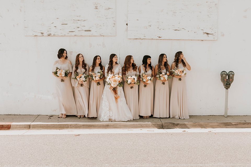 bride in a flowing ballgown and the bridesmaids in neutral colors