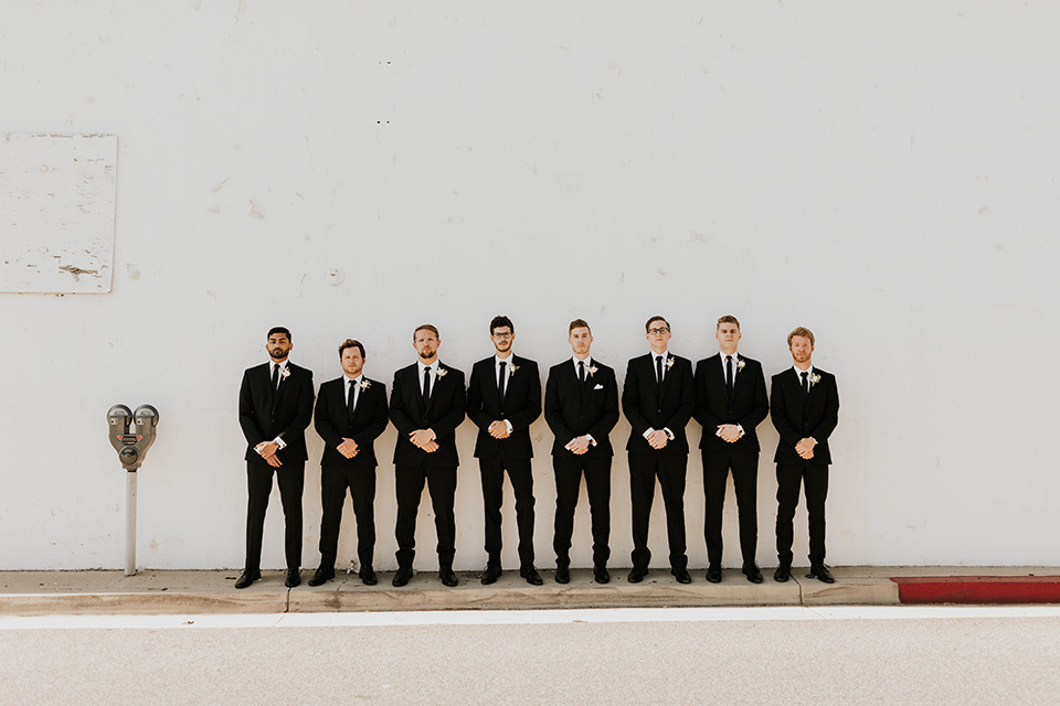bride in a flowing ballgown and the groom in a black suit, the bridesmaids in neutral colors and the groomsmen in black suits and long ties