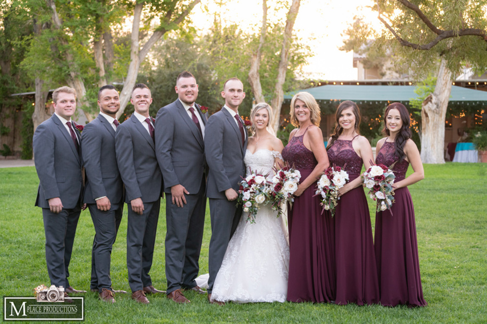 bride in a white lace gown with an off the shoulder detail and long veil and the groom in a dark grey suit and the bridesmaids in burgundy long dresses and the groomsmen in a charcoal grey suits and burgundy long tie