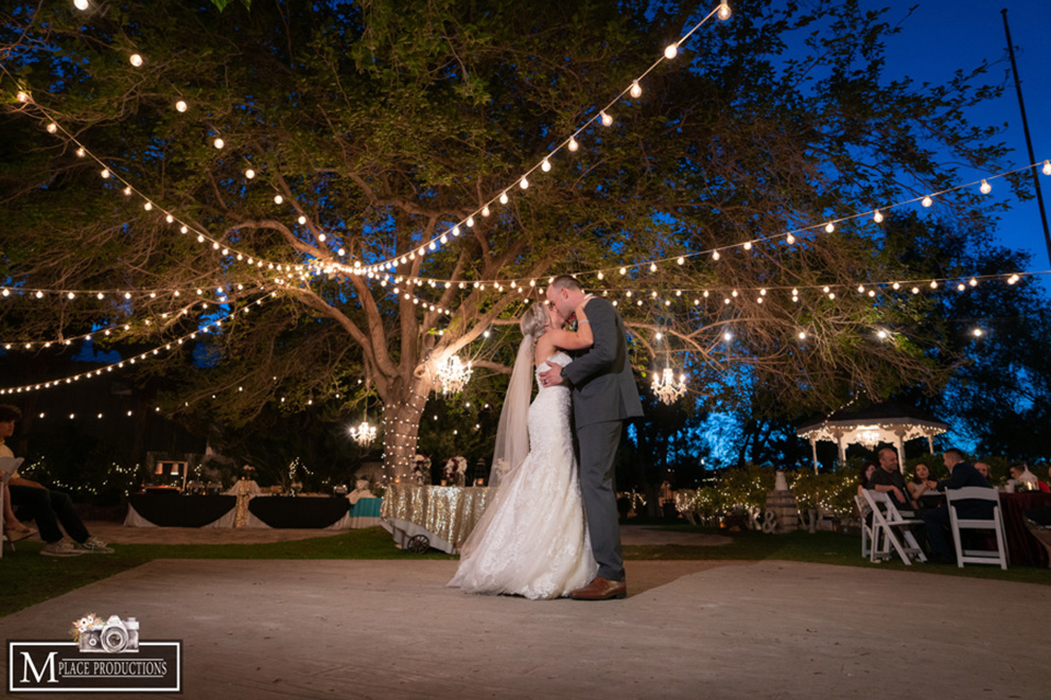 bride in a white lace gown with an off the shoulder detail and long veil and the groom in a dark grey suit first dance