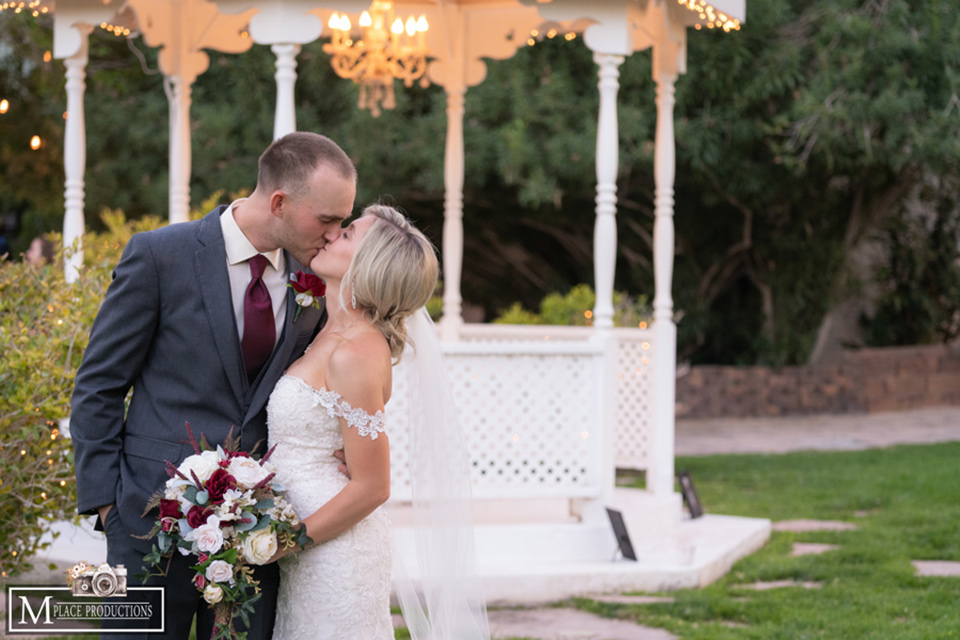 bride in a white lace gown with an off the shoulder detail and long veil and the groom in a dark grey suit kissing