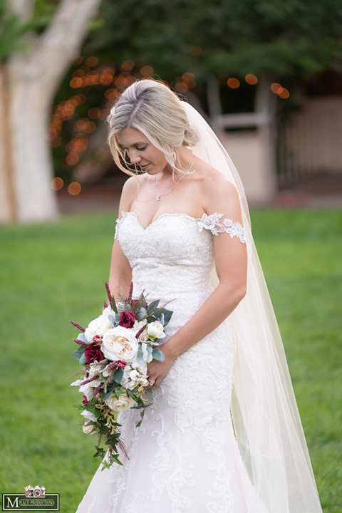 bride in a white lace gown with an off the shoulder detail and long