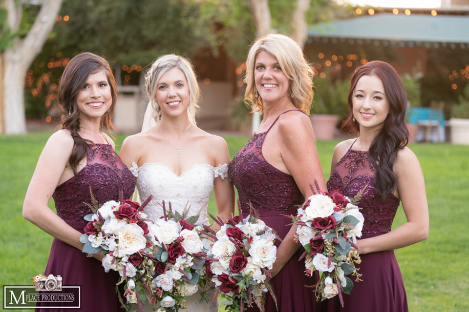 bride in a white lace gown with an off the shoulder detail and long veil and the bridesmaids in burgundy long dresses