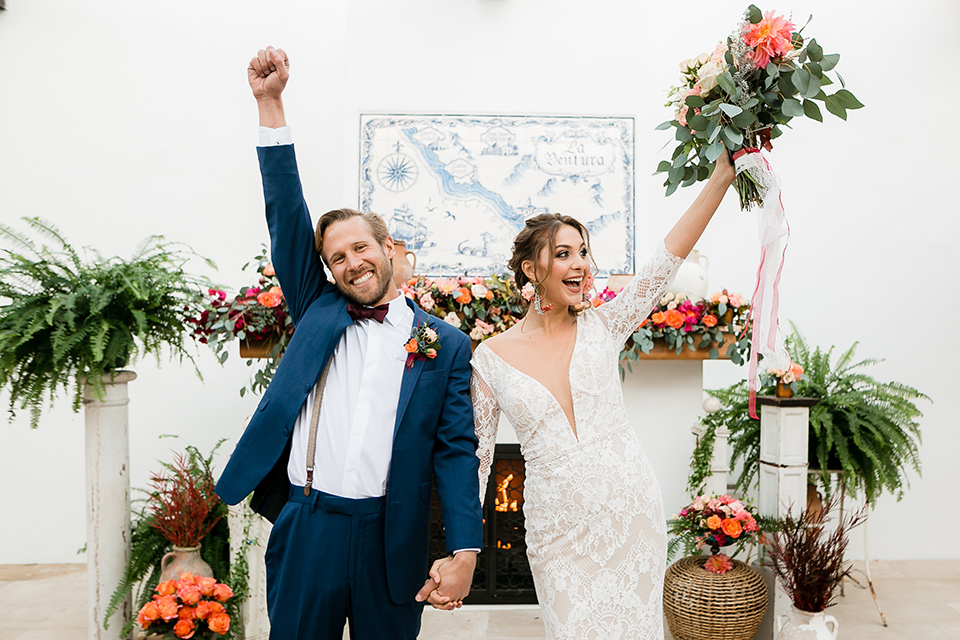 bride in a Spanish inspired lace formfitting gown with and the groom in a dark blue suit with a burgundy bow tie and suspenders, cheering after the ceremony