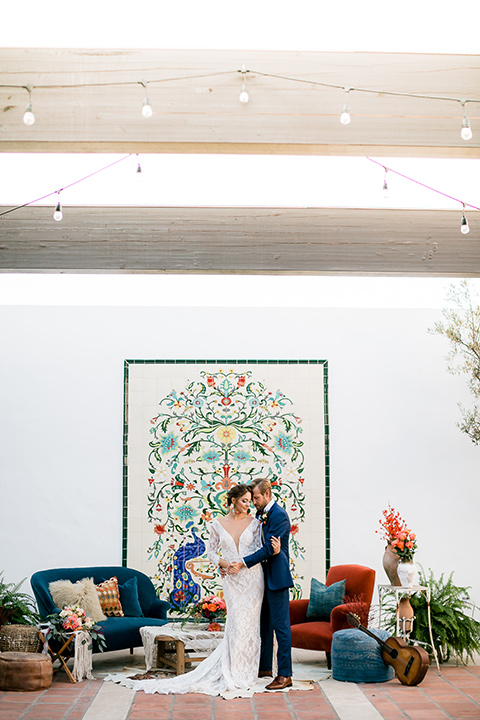 Spanish inspired venue with blue furniture and the bride and groom sitting in the venue, the bride in a lace formfitting gown with sleeves and dark blue suit