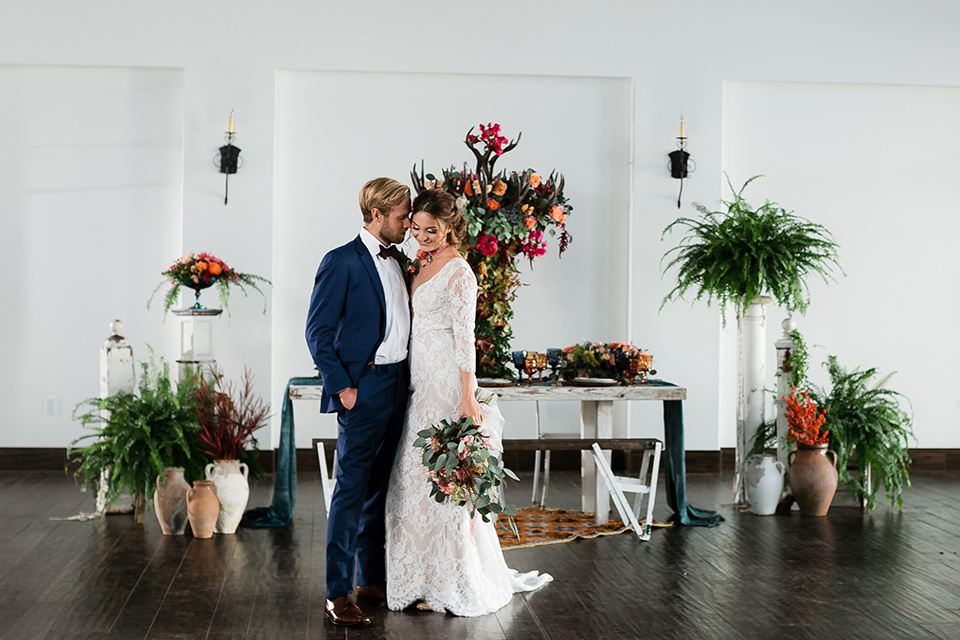 bride in a Spanish inspired lace formfitting gown with and the groom in a dark blue suit with a burgundy bow tie and suspenders, standing in the venue