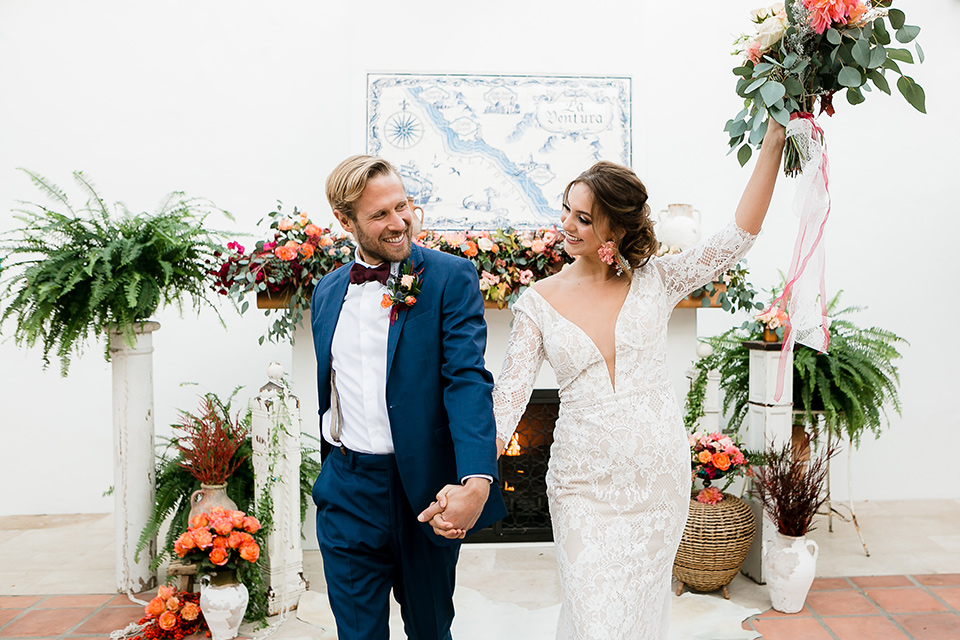 bride in a Spanish inspired lace formfitting gown with and the groom in a dark blue suit with a burgundy bow tie and suspenders, walking down the aisle