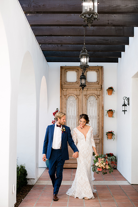 the bride in a lace formfitting gown with sleeves and the groom wore a dark blue suit with a burgundy bow tie