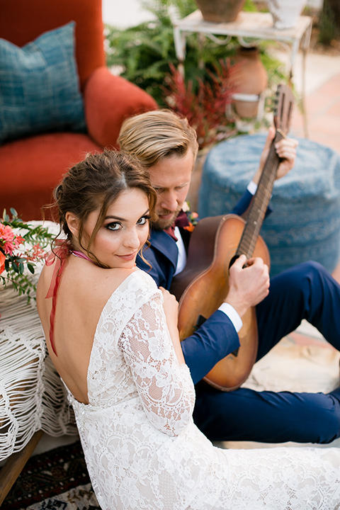 the bride in a lace formfitting gown with sleeves and a floral necklace, the groom in a dark blue suit with a burgundy bow tie sitting and playing a guitar