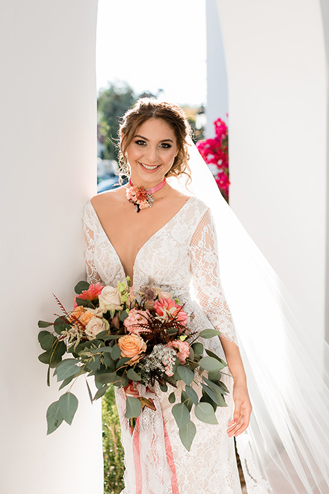 the bride in a lace formfitting gown with sleeves and a floral necklace