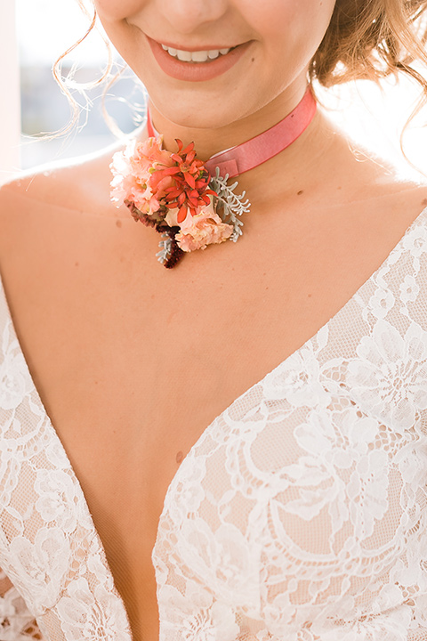 bride in a Spanish lace formfitting gown with sleeves and a floral necklace