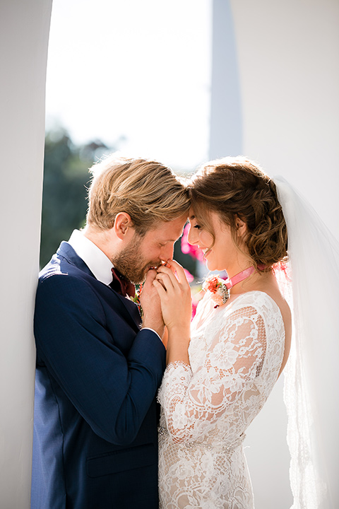 bride in a Spanish lace formfitting gown with sleeves and the groom in a dark blue suit with a burgundy bow tie kissing
