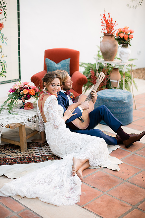 bride in a Spanish lace formfitting gown with sleeves and a floral necklace, the groom in a dark blue suit in a burgundy bow tie