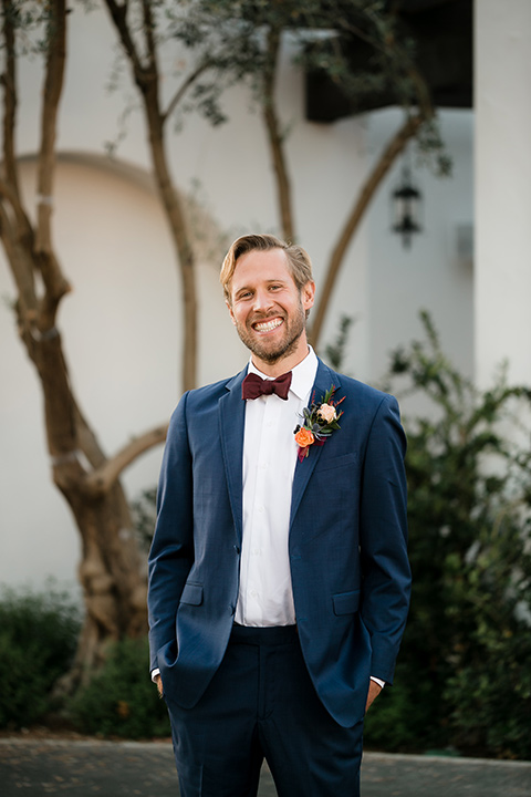 groom in a dark blue suit with a burgundy bow tie