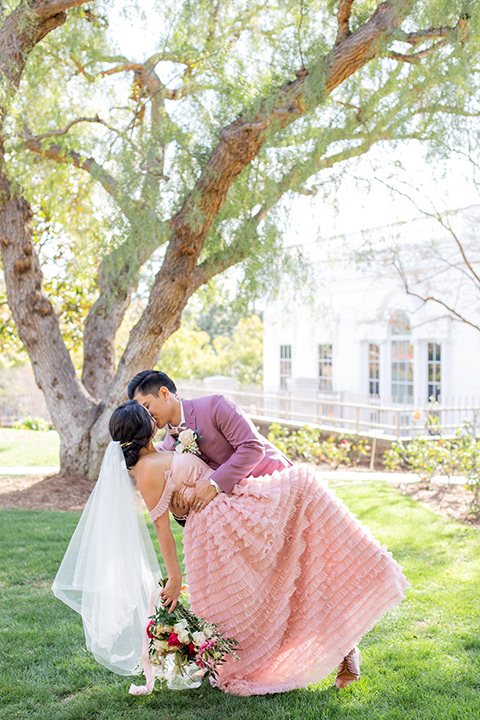 bride in a pink gown with ruffles and the groom in a rose pink suit and a pink bow tie, kissing
