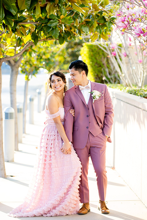 bride in a pink ballgown with ruffles and the groom in a rose pink suit with a pink bow tie