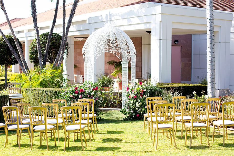 ceremony space with gold chairs and white arch