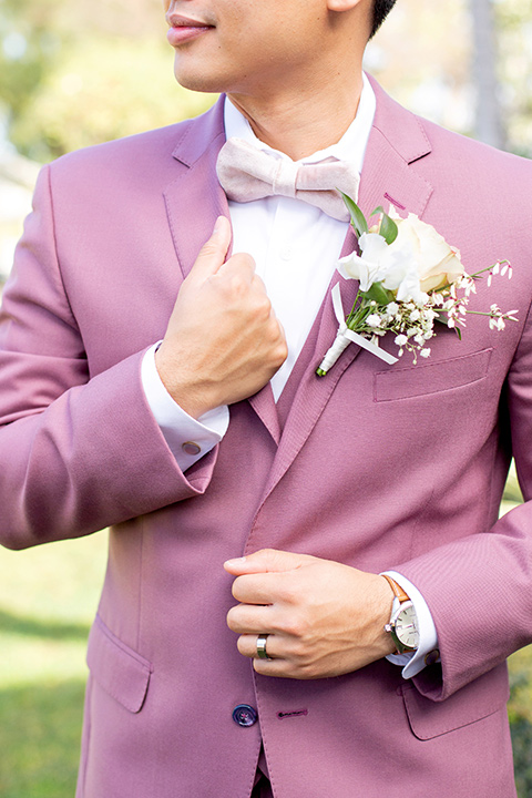 the groom in a rose pink suit with a pink bow tie