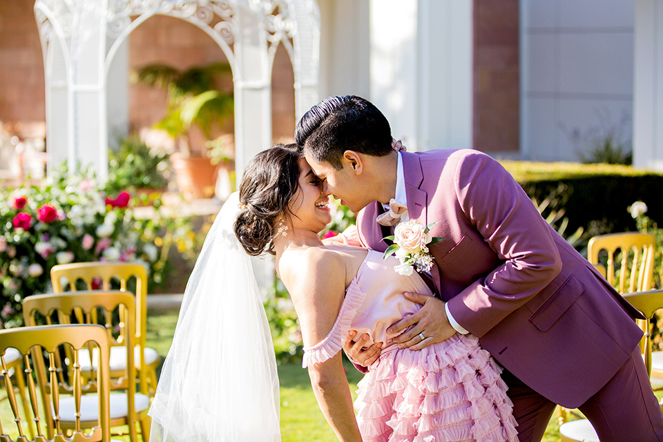 bride in a pink ballgown with ruffles and strapless neckline and the groom in a rose pink suit with a pink bow tie