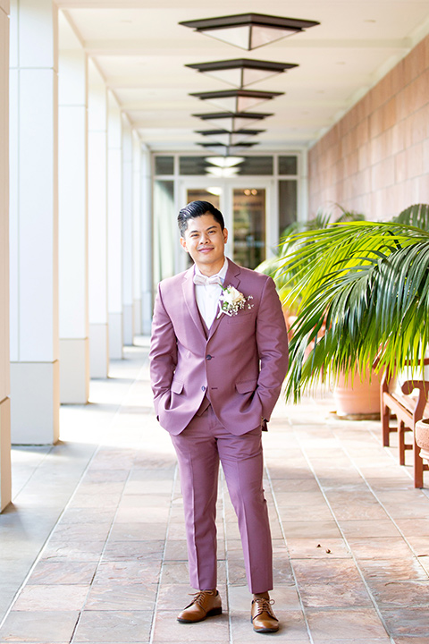 the groom in a rose pink suit and a pink bow tie