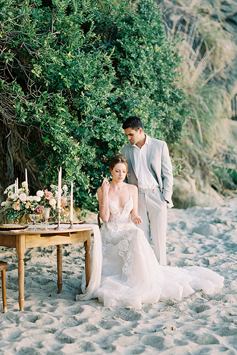 bride in a lace gown with a flowing tulle skirt and thin straps groom in a light grey suit with a white shirt and no tie sitting at table