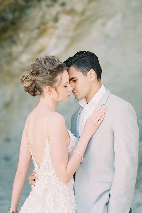 bride in a lace gown with a flowing tulle skirt and thin straps groom in a light grey suit with a white shirt and no tie hugging close by the ocean