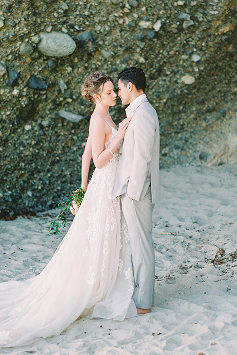 bride in a lace gown with a flowing tulle skirt and thin straps groom in a light grey suit with a white shirt and no tie embracing
