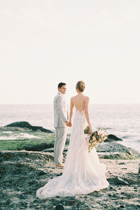 bride in a lace gown with a flowing tulle skirt and thin straps groom in a light grey suit with a white shirt and no tie walking close by the ocean