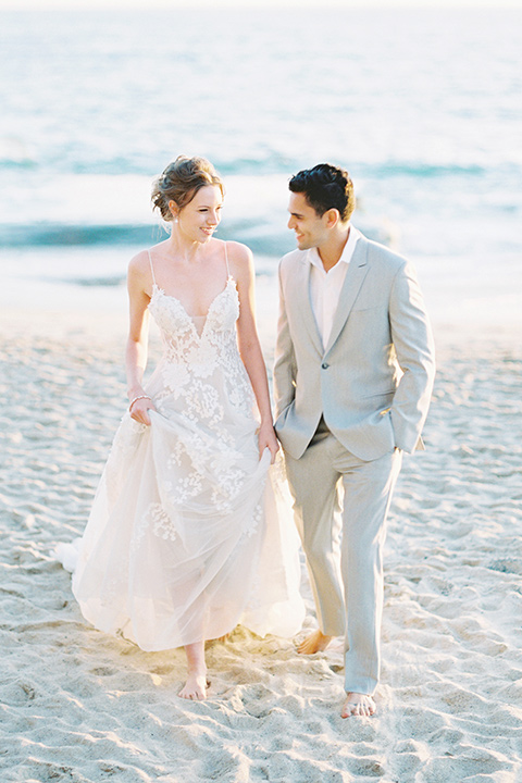 bride in a lace gown with a flowing tulle skirt and thin straps groom in a light grey suit with a white shirt and no tie walking towards camera
