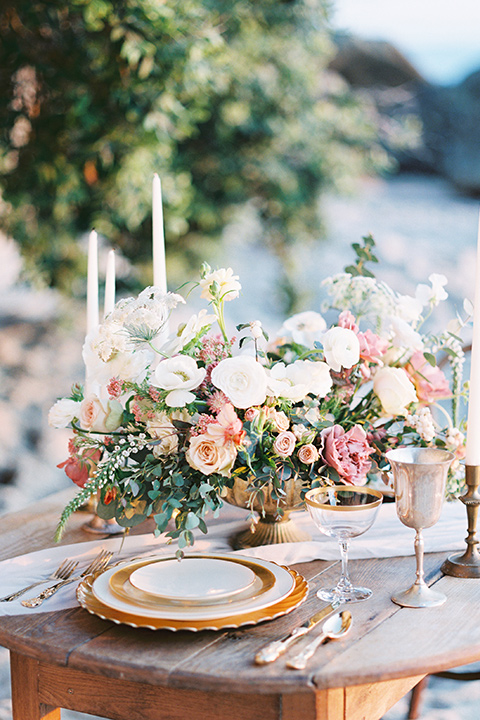 wooden table with white and terracotta flatware and tall white candles