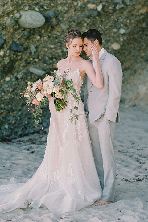 bride in a lace gown with a flowing tulle skirt and thin straps groom in a light grey suit with a white shirt and no tie