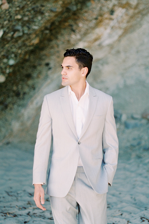 groom in a light grey suit with a white shirt and no tie