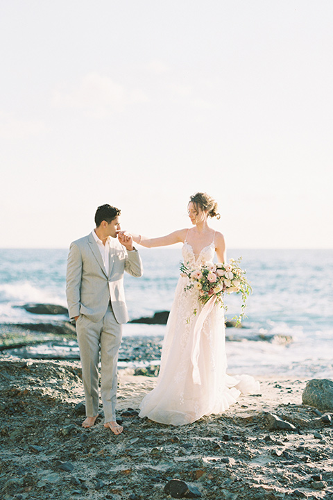 bride in a lace gown with a flowing tulle skirt and thin straps groom in a light grey suit with a white shirt and no tie walking close by the ocean and kissing