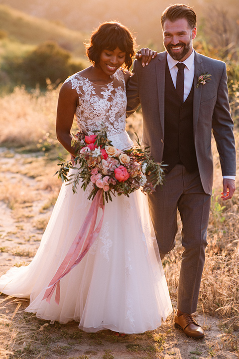 bride in a flowing ivory gown with a high neckline and the groom in a café brown suit with a long tie