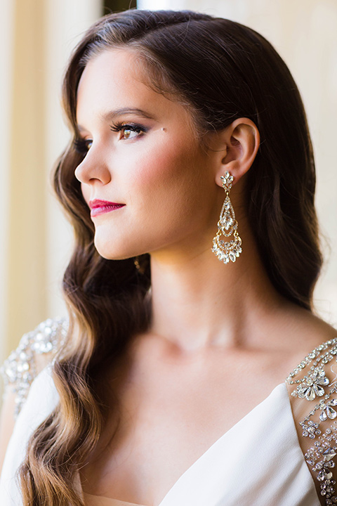 bride with a soft fingerwave hair style with delicate makeup and gold earrings