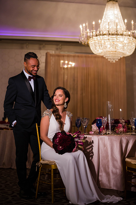 bride with a soft finger wave hair style with delicate makeup and gold earrings, the groom in a navy tuxedo with a black satin lapel and a purple bow tie sitting at the table