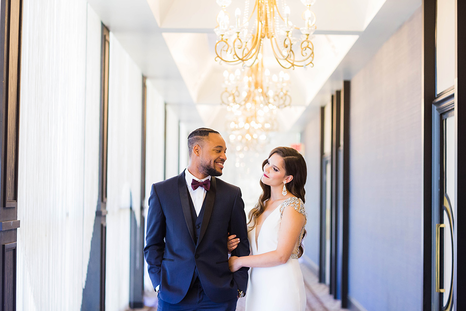 bride in a satin white formfitting gown with a plunging neckline and a trumpet train skirt holding a bouquet of purple flowers the groom in a navy tuxedo with a black satin lapel and a purple bow tie smiling at each other in the hallway