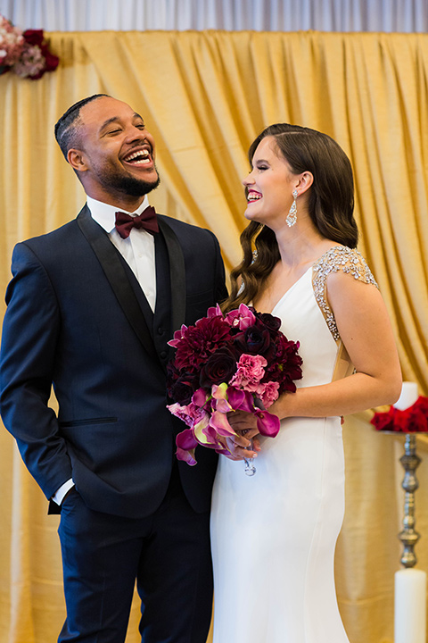 bride with a soft finger wave hair style with delicate makeup and gold earrings, the groom in a navy tuxedo with a black satin lapel and a purple bow tie laughing